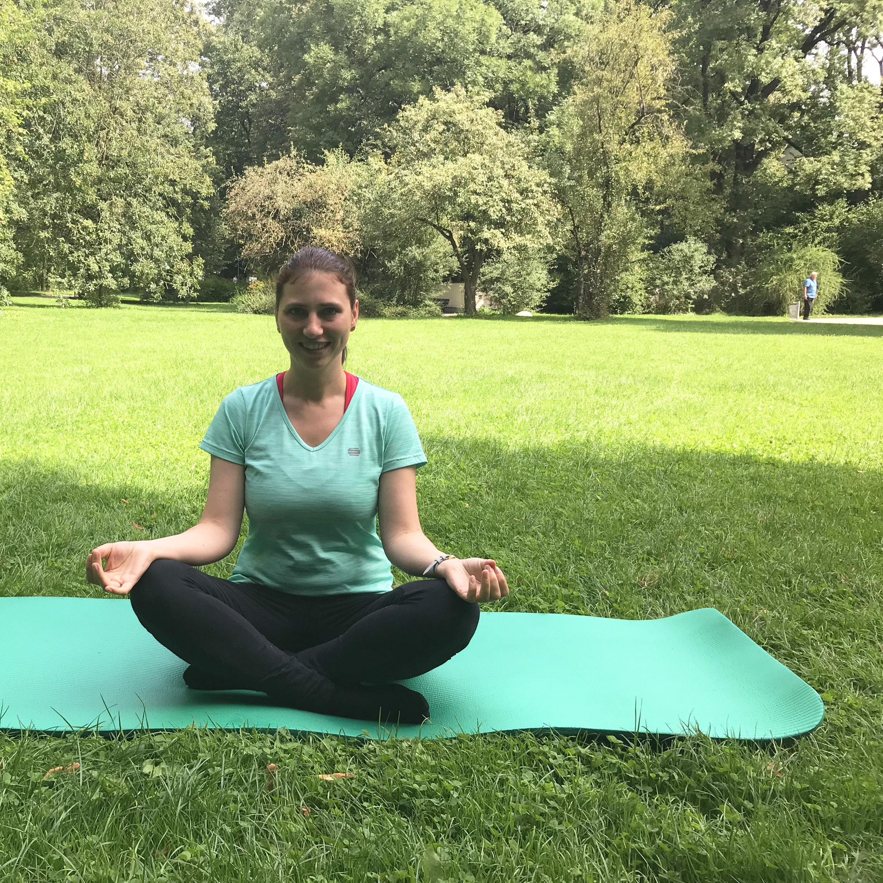 Sarah meditiert im Park auf einer Yogamatte